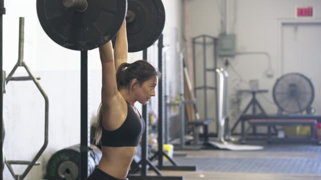 stockvideo's en b-roll-footage met ms strong young woman lifting weights in a gym - zwaar