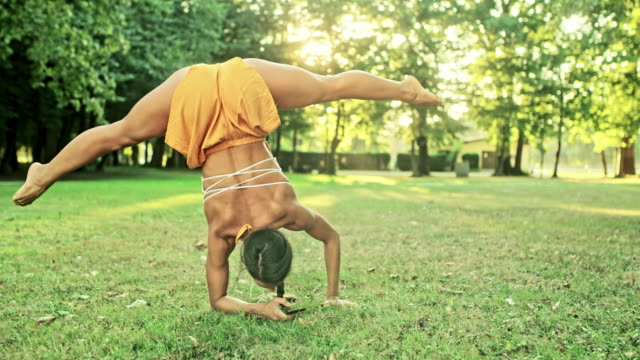 ms strong young woman practicing yoga, using smart phone upside-down in sunny park - avambraccio video stock e b–roll