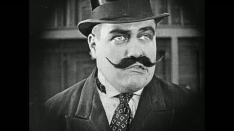 vidéos et rushes de 1919 a strongman (charles a. post) with a big mustache and a top hat surveilles theater and pushes his assistant (molly malone) who carries five suitcases, one hanging from her mouth, into men (fatty arbuckle & buster keaton) - 1910 1919