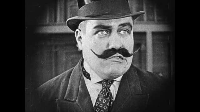1919 a strongman (charles a. post) with a big mustache and a top hat surveilles theater and pushes his assistant (molly malone) who carries five suitcases, one hanging from her mouth, into men (fatty arbuckle & buster keaton) - 無声映画点の映像素材/bロール