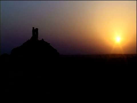structure said to be tower of babel in silhouette against orange sunset iraq - irak stock-videos und b-roll-filmmaterial