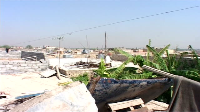 struggle for survival of the poor; iraq: baghdad: ext rundown back alley with people milling about, horse and cart passes in foreground breeze blocks... - rubble stock-videos und b-roll-filmmaterial