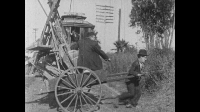 1915 struggling charlie chaplin rolls backward while pulling a horse cart for boss and nearly get hit by streetcar - horse cart stock videos and b-roll footage