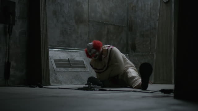 Struggling clown sitting on floor of mental asylum wearing straight jacket / Cedar Hills, Utah, United States