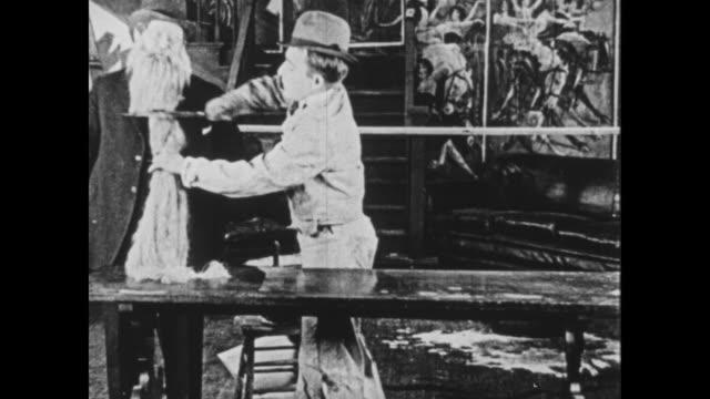 vidéos et rushes de 1925 struggling wallpaper assistant obliviously glues man's beard to table - mesurer