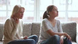 Stubborn annoyed young daughter ignoring worried stressed old mother arguing