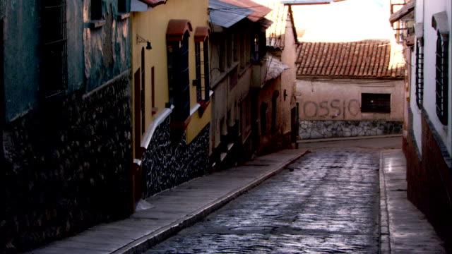 stucco and brick houses crowd a narrow cobblestone street in bolivia. available in hd. - れんが造りの家点の映像素材/bロール