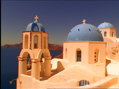 stucco church with blue domes overlooking sea / oia, santorini, greece - イア点の映像素材/bロール
