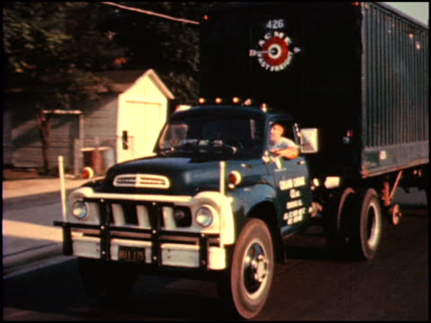 Studebaker semi turns corner camera tracks as truck drives on city street / MS driver side front end of medium duty diesel truck / WS front...
