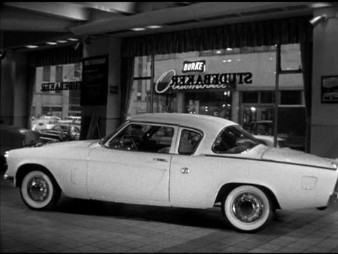 studebaker starliner designed by raymond loewy, vs new designs, packard concept car pan american. detroit: driving up street in rain, moving under... - raymond loewy video stock e b–roll