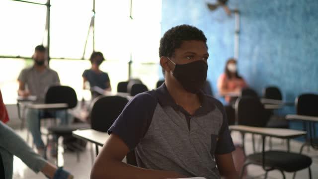 vídeos de stock, filmes e b-roll de aluno que vai à aula - usando máscara facial - de braço levantado