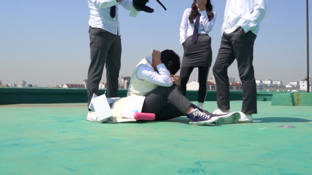 vídeos y material grabado en eventos de stock de a student bullied by other youths on a rooftop floor - bullying
