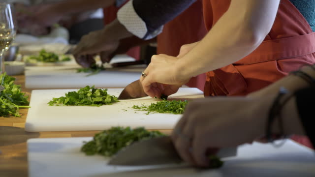 Student chefs chopping parsley