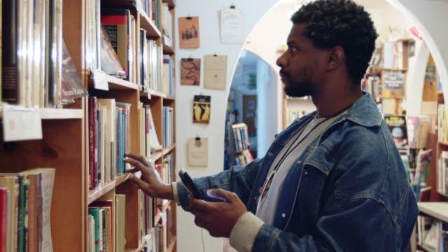 vidéos et rushes de étudiant choisissant des livres dans la librairie - un seul homme d'âge moyen