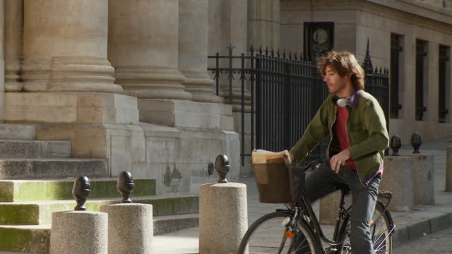 vídeos y material grabado en eventos de stock de ms td tu student cycling down street, dismounting and locking up bike, entering sorbonne university, rue de la sorbonne, paris, france - aparcar