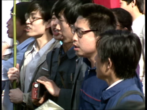student demonstrations in beijing; protesters along with placards and banneres / nurses watching demonstrators / man handing out leaflets / flags and... - beijing stock videos & royalty-free footage