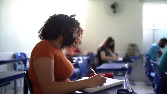 stockvideo's en b-roll-footage met student die examen in klaslokaal doet - exam