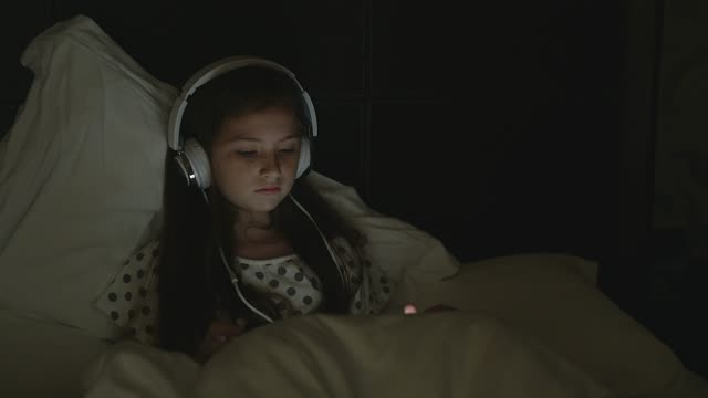 student e-learning wearing headphones watching online tutorials in the night at home. - only teenage girls stock videos and b-roll footage