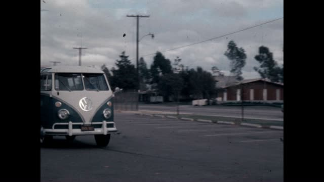 student film of a vw bus driving through a parking lot - bus stock videos & royalty-free footage