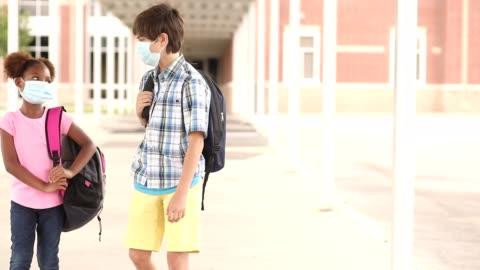 student vänner gå till klassen bär masker för covid-19. - skolbyggnad bildbanksvideor och videomaterial från bakom kulisserna