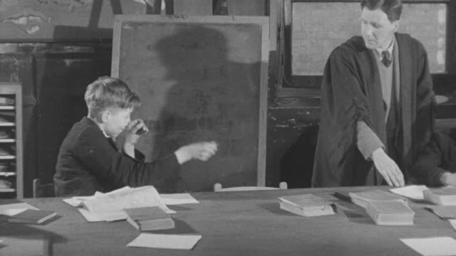 1947 MONTAGE Student getting in trouble with rubber band in classroom / United Kingdom