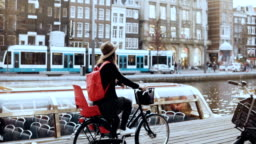 Student girl cycling bicycle along a river quay. Local commuter. Female in hat cruising on a city bike. Slow motion