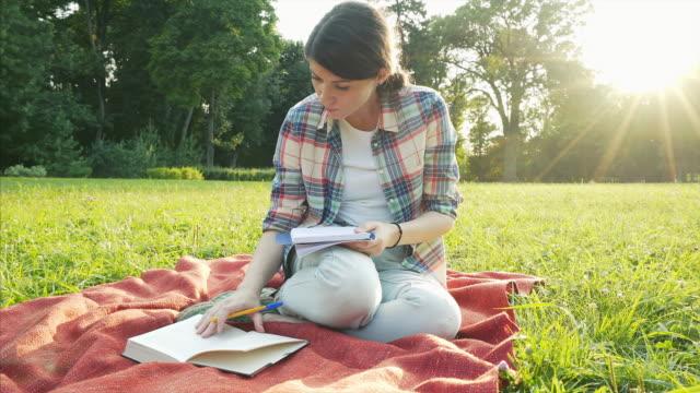 vidéos et rushes de fille d'étudiants étudient au parc. - littérature