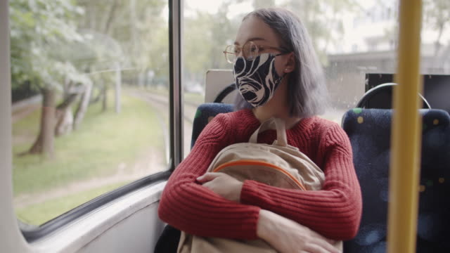 student girl using public transportation to go to the school wearing a protective face mask during covid-19 pandemic. back to school and new normal concept. - back to school stock videos & royalty-free footage