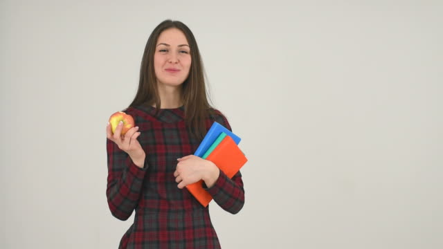 student girl with books eats apple - standing stock videos & royalty-free footage