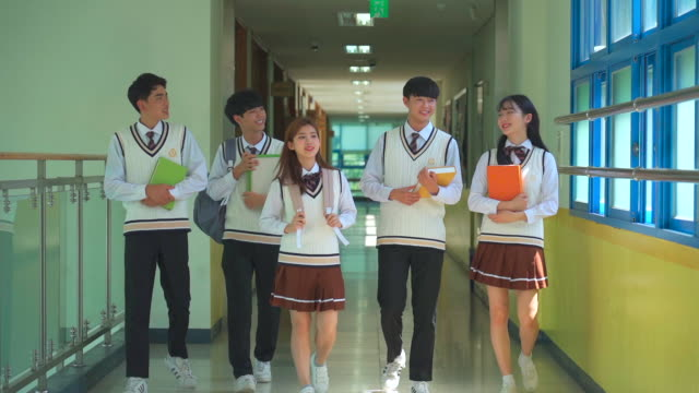 a student group walking and holding a book in the hallway of classroom - 制服点の映像素材/bロール