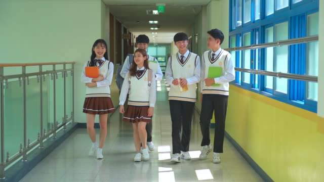 a student group walking and holding a book in the hallway of classroom - south korea stock videos & royalty-free footage