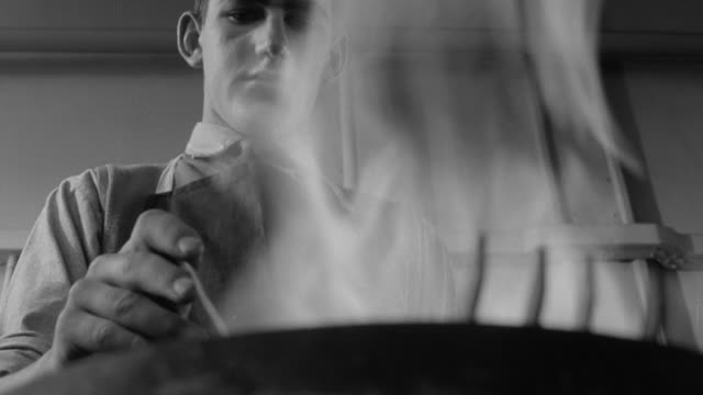 1960 b/w student heating a metal instrument in fire during metallurgy class / united kingdom - metallurgy stock videos & royalty-free footage