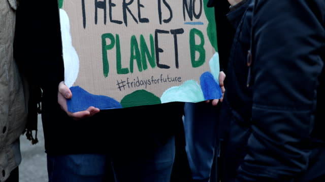 a student is being interviewed by a tv station holding a poster with the inscription and hashtag #fridaysforfuture striking high school students... - holding poster stock videos & royalty-free footage