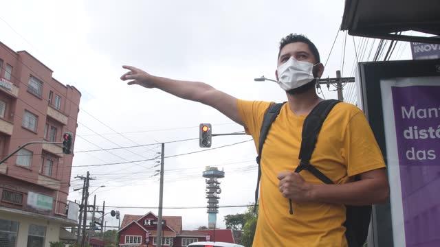 vídeos de stock, filmes e b-roll de estudante esperando o ônibus, usando máscara. - ônibus