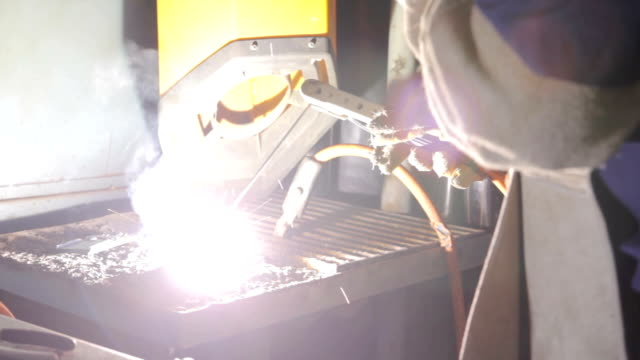 Student practice welding in a workshop