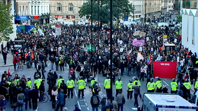 stockvideo's en b-roll-footage met student protest march / marchers at moorgate; high angle view police vans zoom in on crowd of demonstrators gathered in road / various high angle... - zoom out