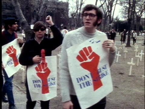 student protesters walk past crosses erected on harvard yard during the sit-in at harvard university in cambridge, massachusetts. - protestor stock videos & royalty-free footage