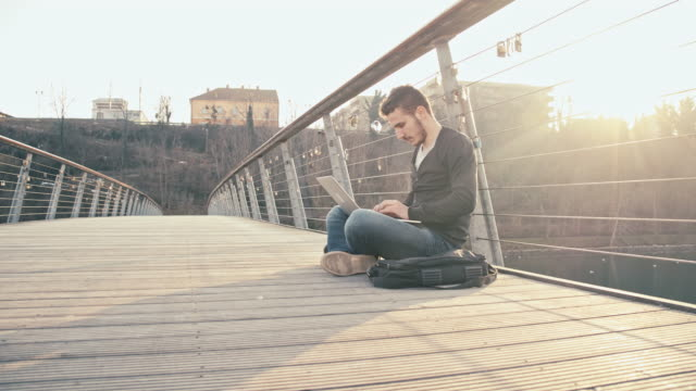 WS Student Rejoicing While Using Laptop On Bridge