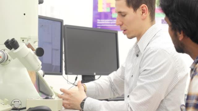 student researcher learning and observing senior colleague - microscopio elettronico a scansione video stock e b–roll