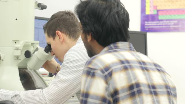 studente ricercatore apprendimento e osservazione senior collega - microscopio elettronico a scansione video stock e b–roll