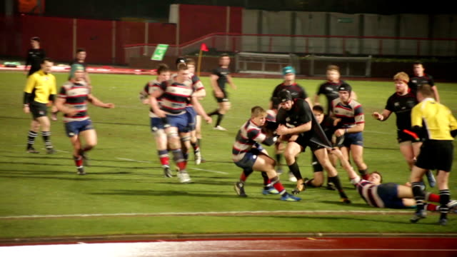 vídeos de stock e filmes b-roll de uk student rugby match hard tackle on grass pitch at night no - tackling