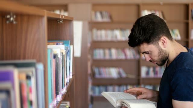 student searching books - biblioteca video stock e b–roll