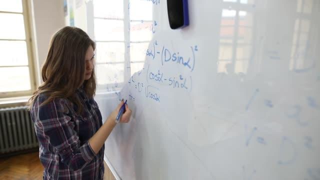 vídeos de stock, filmes e b-roll de estudante que resolve o problema da matemática - estudante universitária
