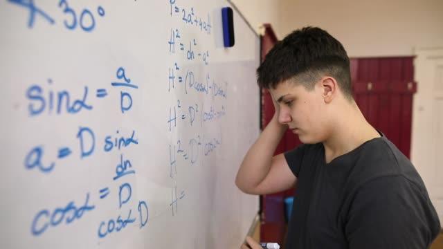 vídeos de stock, filmes e b-roll de estudante que resolve o problema da matemática - perguntando