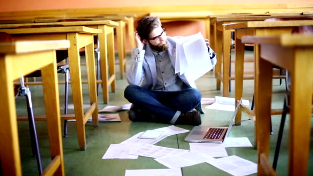 Student struggling with papers.