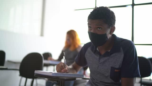 vídeos de stock, filmes e b-roll de aluno estudando em sala de aula - usando máscara facial - exam