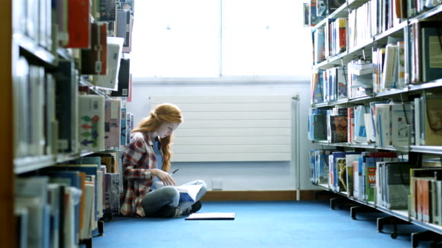 student studying in library - bibliothek stock-videos und b-roll-filmmaterial