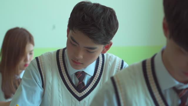 student taking an examinanton in the classroom - 試験点の映像素材/bロール