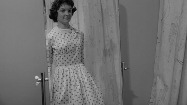 stockvideo's en b-roll-footage met 1960 b/w student trying on dress in fashion design class / united kingdom - jurk