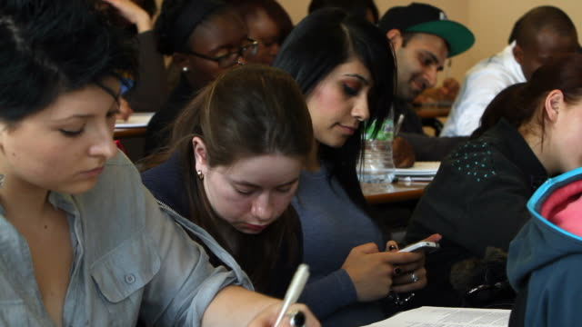 vídeos de stock e filmes b-roll de aluno utiliza cellphone para texto durante a aula - pessoas ao fundo
